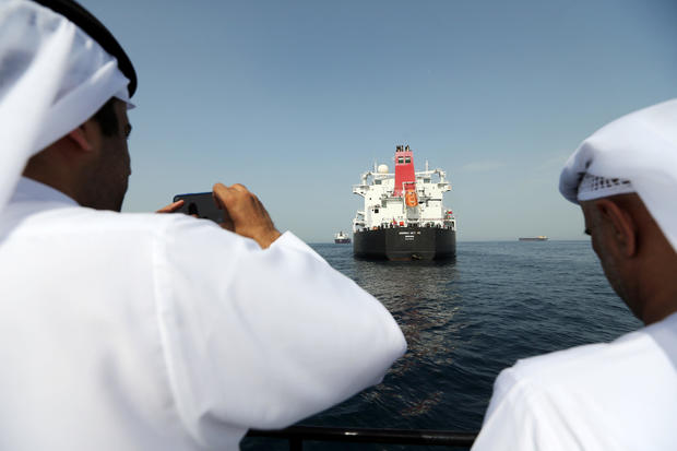 Port officials take a photo of a damaged Andrea Victory ship at the Port of Fujairah