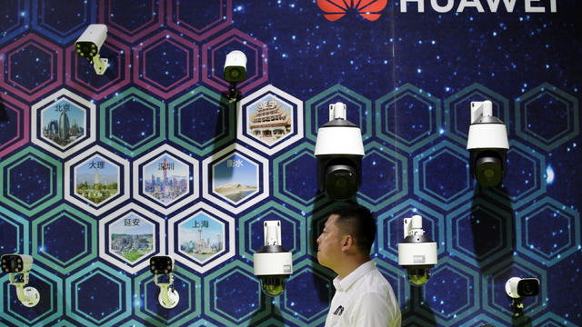 Man walks past surveillance cameras displayed at a Huawei booth at an exhibition during the World Intelligence Congress in Tianjin