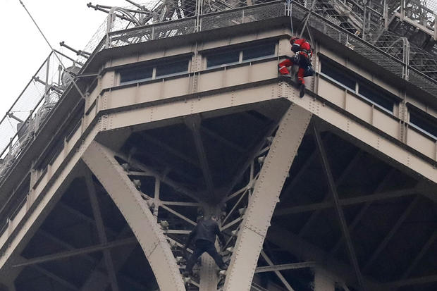 A rescue worker, top in red, hangs from the Eiffel Tower while a climber is seen below him between two iron columns May 20, 2019, in Paris.