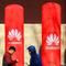 People walk past logos of Huawei in Huaian