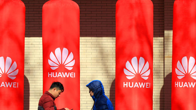 People walk past logos of Huawei in Huaian