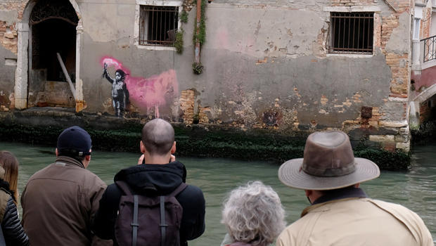 People look at the new work of British street artist Banksy, on the outer wall of a house along the Rio de Ca Foscari canal in Venice