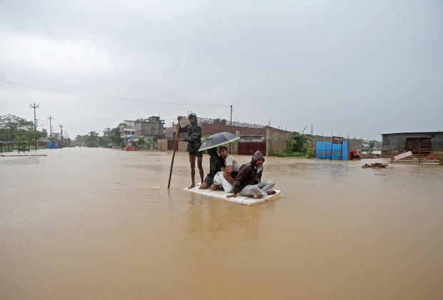 Villagers use a makeshift raft to cross a flooded area on the outskirts of Agartala