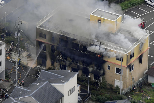 An aerial view shows firefighters battling fires at the site where a man started a fire after spraying a liquid at a three-story studio of Kyoto Animation Co. in Kyoto, western Japan, in this photo taken by Kyodo