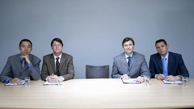 Four businessmen sitting next to empty chair in boardroom, portrait
