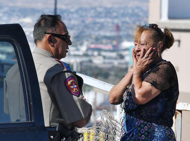 Virginia Chacon reacts as she tells her survival story to a police officer outside the Walmart where a shooting left 20 people dead in El Paso, Texas, on Aug. 4, 2019.