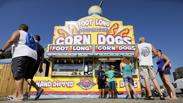 Fairgoers line up to get a corn dog at a concession stand during the opening day of the Iowa State Fair in Des Moines, Iowa, Aug. 9, 2018.