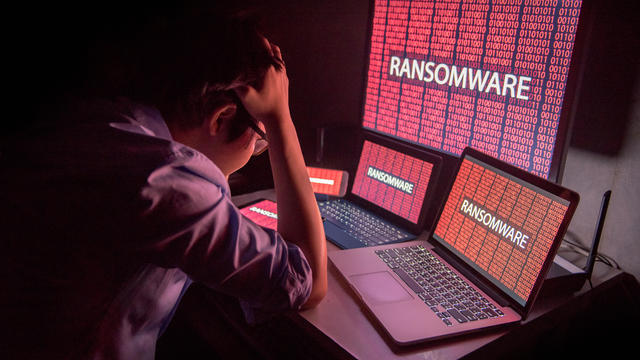 Young Asian male frustrated by ransomware cyber attack