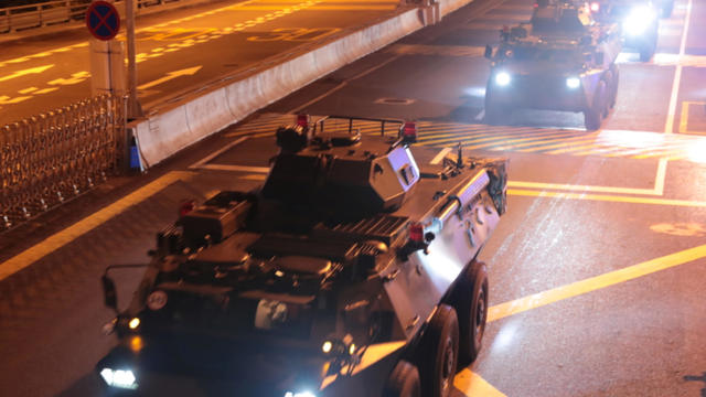 Military vehicles of the Chinese People's Liberation Army (PLA) pass Huanggang Port for a routine troop rotation in Hong Kong