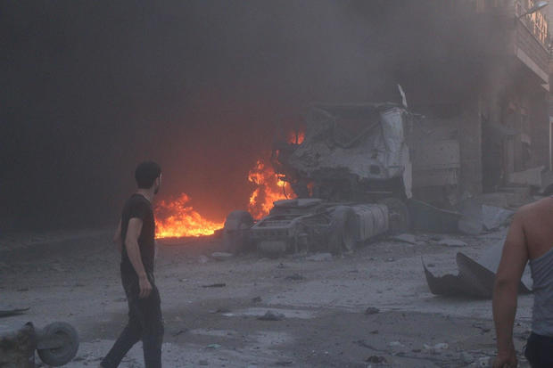 People walk next to fire, debris and a damaged truck after a deadly airstrike, said to be in Maarat al-Numan