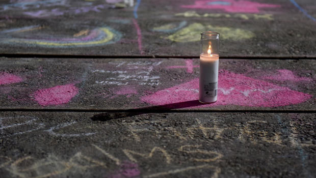 Messages written in sidewalk chalk are seen at the University of Texas of the Permian Basin following Saturday's shooting in Odessa