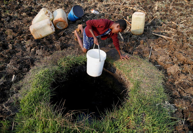 A woman fetches water from a well in Warren Park suburb, Harare