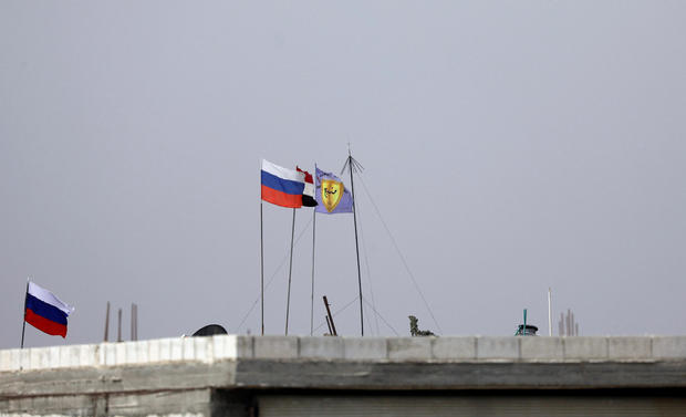 Russian, Syrian and Manbij military council flags flutter near Manbij