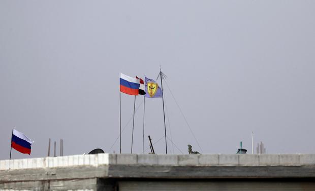Russian, Syrian and Manbij military council flags flutter near Manbij