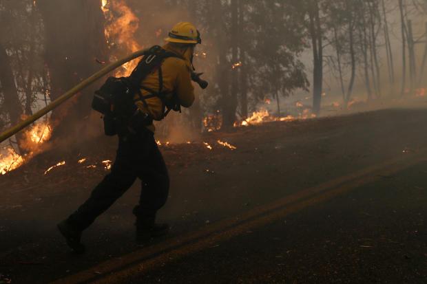 A firefighter pulls a hose along Chalk Hill Road as he battles the wind-driven Kincade Fire in Windsor, California, October 27, 2019.