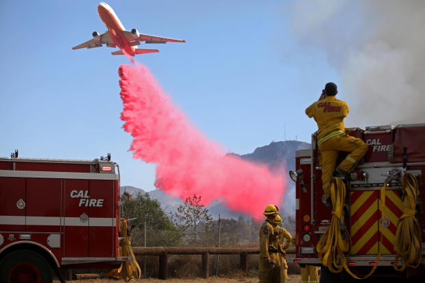 Cal Fire firefighters look on as a plane drops fire retardant on the Maria Fire in Santa Paula, California, November 1, 2019.