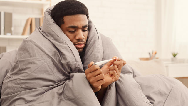 Ill man covered with blanket holding thermometer