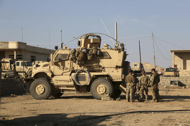 U.S. Army soldiers stand outside their armored vehicle on a joint base with the Iraqi army south of Mosul, Iraq, on February 23, 2017.