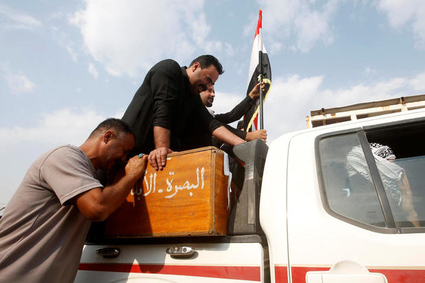 An Iraqi man mourns over the coffin of a demonstrator who was killed at anti-government protests, during a funeral in Basra