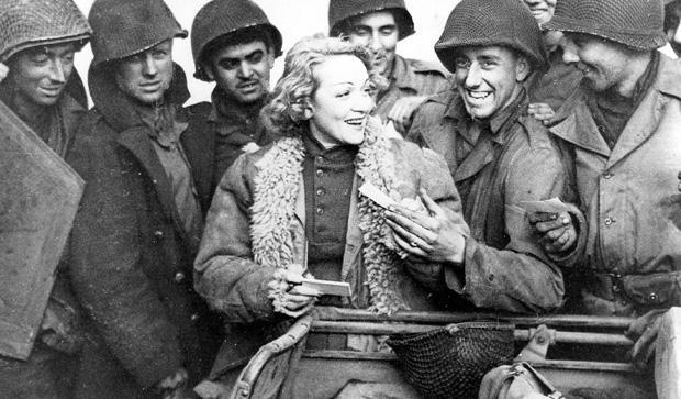 Marlene Dietrich with American soldiers, 1943. Image shot 1943. Exact date unknown.