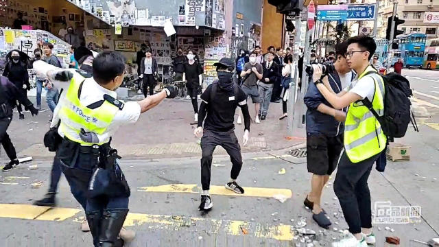 A still image from a social media video shows a police officer aiming his gun at a protester in Sai Wan Ho, Hong Kong
