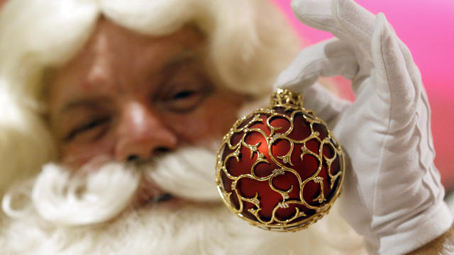 An actor dressed as Father Christmas displays a Christmas bauble to mark the annual opening of Harrods Christmas-themed shop, at Harrods department store in London