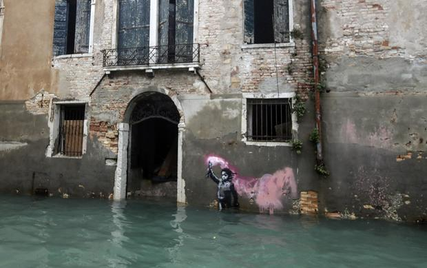 Banksy artwork of a refugee in a life jacket is now under floodwater in Venice