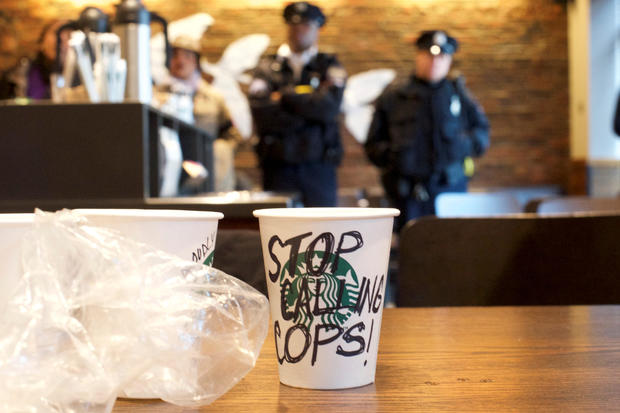 "A Starbucks coffee cup with ""Stop Calling Cops!"" written on the side sits on a table as police monitor protestors demonstrating inside a Center City Starbucks, where two black men were arrested, in Philadelphia"
