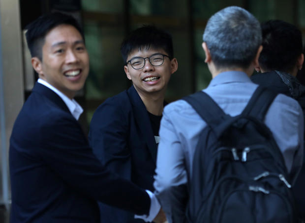 Winning candidate Kelvin Lam and activist Joshua Wong greet people and thank them for their support, outside South Horizons Station, in Hong Kong