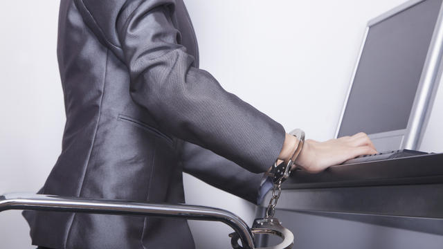 Young businesswoman handcuffed to her office chair