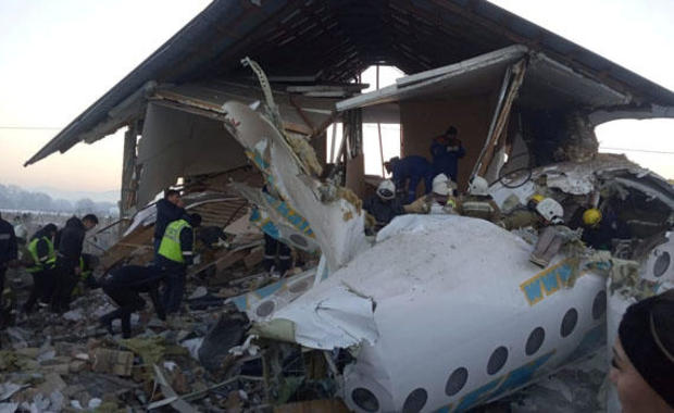 Emergency and security personnel are seen at the site of the plane crash near Almaty