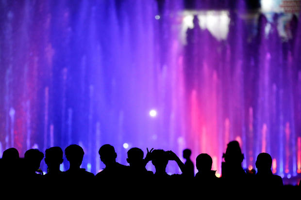People watch a water show at the National Monument complex during New Year's Eve celebrations in Jakarta, Indonesia, December 31, 2019.