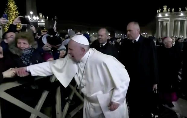 A woman grabs Pope Francis' hand and yanks him toward her at St. Peter's Square at the Vatican in this still image taken from a video December 31, 2019.
