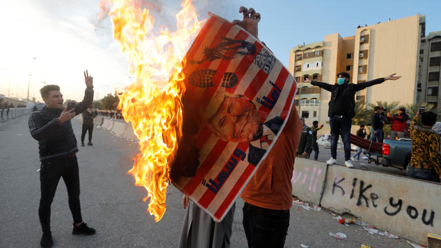 A protester holds a placard with an illustration of President Trump burning outside the U.S. Embassy in Baghdad, Iraq, January 1, 2020, during a protest to condemn airstrikes against an Iran-backed militia.