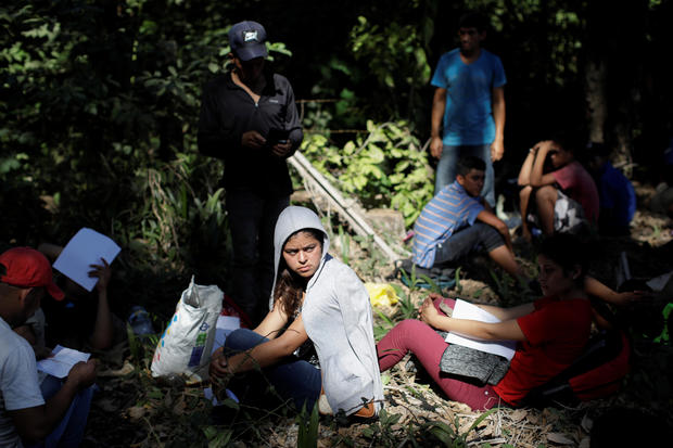 Migrants, mainly from Central America and marching in a caravan, hold forms to apply for asylum, near Frontera Hidalgo, Chiapas