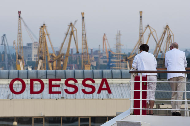 Passengers of a cruise ship look out at the port of Odessa, Ukraine