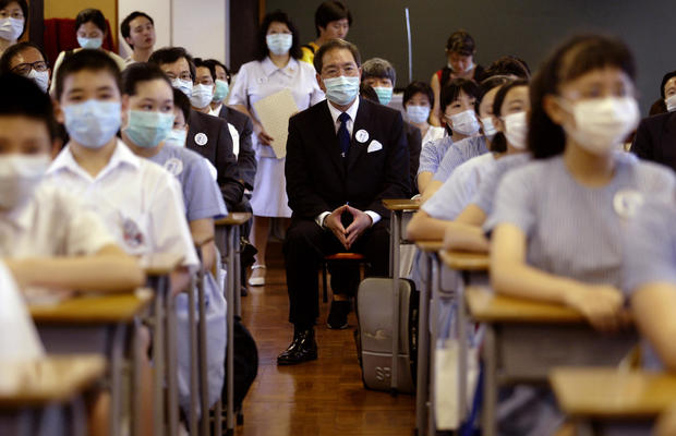 Secretary for Education and Manpower Arthur Li Kwok-cheung attends a lesson in a class in Baptist Lui Ming Choi Primary School in Shatin on the first day of returning to school since the SARS outbreak.  12 May 2003