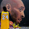 A boy in Kobe Bryant's shirt looks at the mural by Jorit