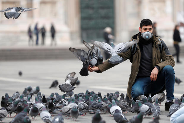 Man in a face mask feeds pigeons in Milan