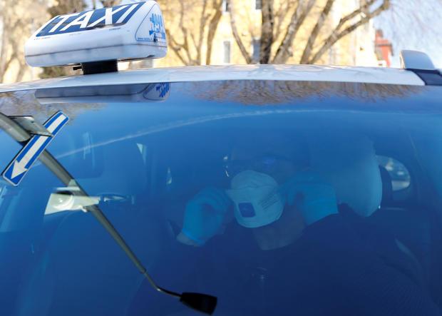 Seminario, a taxi driver in Milan, wears a protective mask