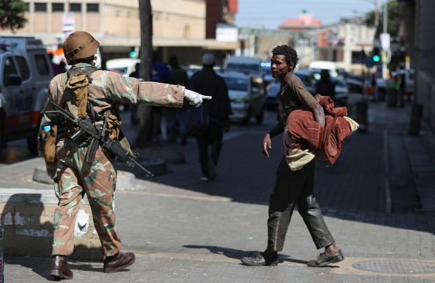 A member of the South African National Defence Forces gestures to a homeless men during their patrols on the first day of a nationwide lockdown in Johannesburg
