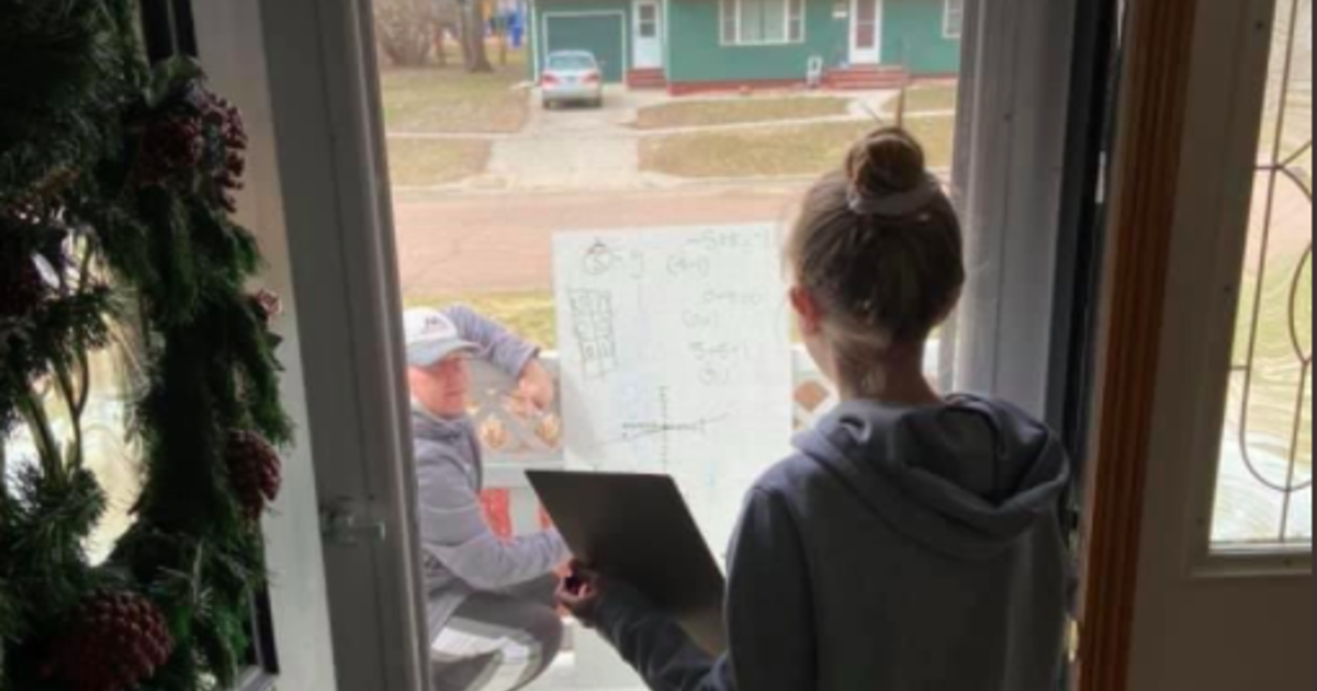 Math teacher helps student with homework while social distancing on front porch