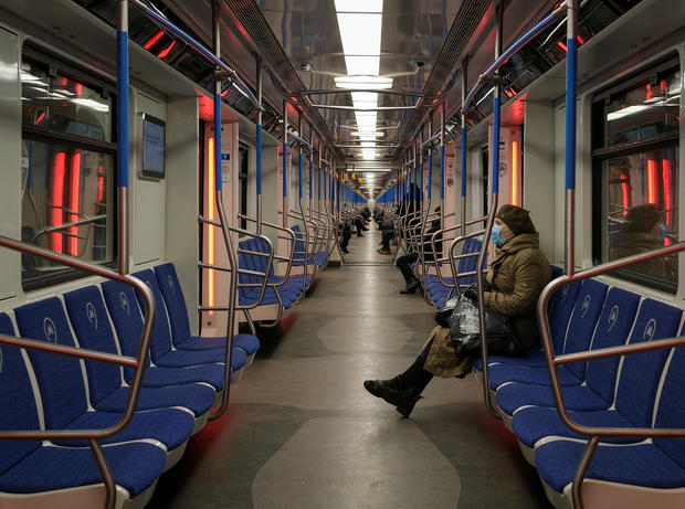FILE PHOTO: A woman wearing a protective mask rides in a metro train in Moscow