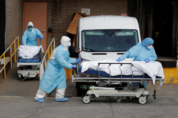Healthcare workers wheel bodies deceased people from Wyckoff Heights Medical Center during outbreak of coronavirus disease (COVID-19) in New York