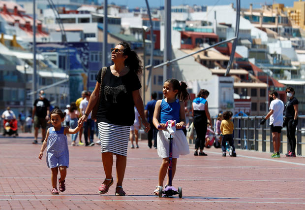 Family members walk at promenade of Las Canteras beach after restrictions were partially lifted for children for the first time in six weeks, following the coronavirus disease (COVID-19) outbreak on the island of Gran Canaria