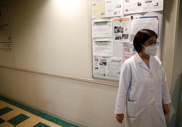 Fumie Sakamoto, a nurse of St. Luke's International Hospital stands in front of her office as she talks to Reuters reporters in Tokyo