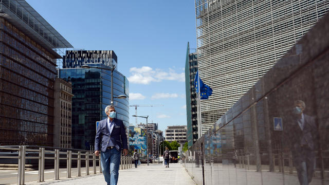 A man wearing a face mask walks past the European Commission headquarters as the spread of coronavirus disease (COVID-19) continues in Brussels