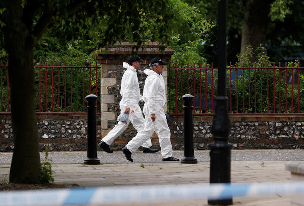 Police officers in forensic suits walk along the park where the scene of multiple stabbings took place, in Reading