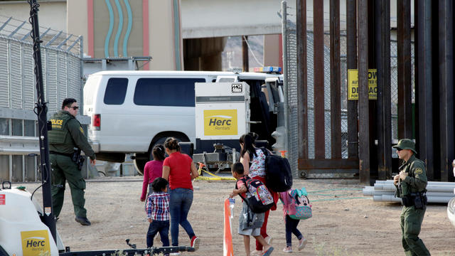 FILE PHOTO: CBP agents look at migrants who crossed illegally into El Paso, Texas, U.S. to turn themselves in to ask for asylum as seen from Ciudad Juarez