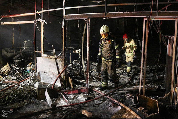 Firefighters inspect the site of an explosion at a medical clinic in the north of the Iranian capital Tehran